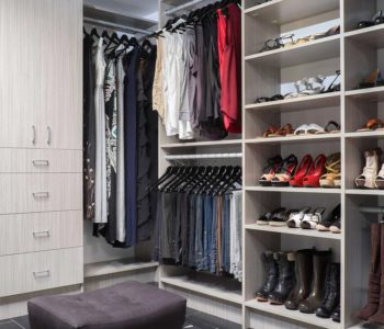 Walk-in closet with clothes hanging and shoe shelves and an ottoman