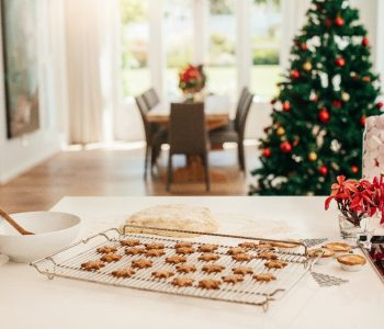 A close up of a kitchen counter with a tray of baked cookies with a Christmas tree in the background.